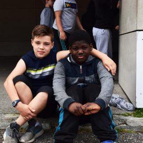 Photo d'une accolade entre deux élèves assis de l'école Michoun